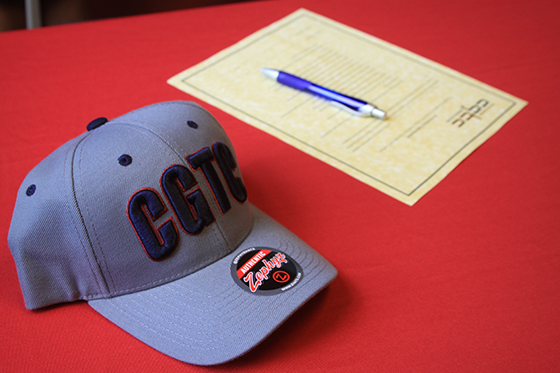 Picture is a gray, CGTC baseball cap and a document to be signed.