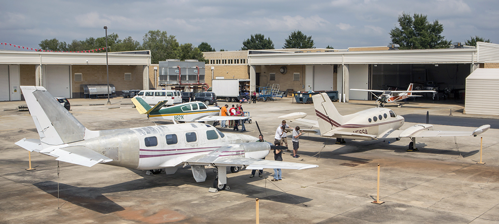 Students working on two small airplanes on the Warner Robins campus.