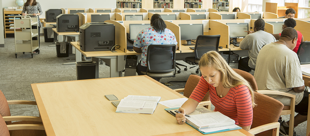 Young woman sitting at desk in library reading a text book while several other students work on computers in the background in a library.