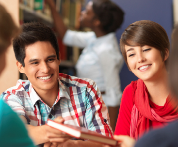 Image of two college students smiling in library