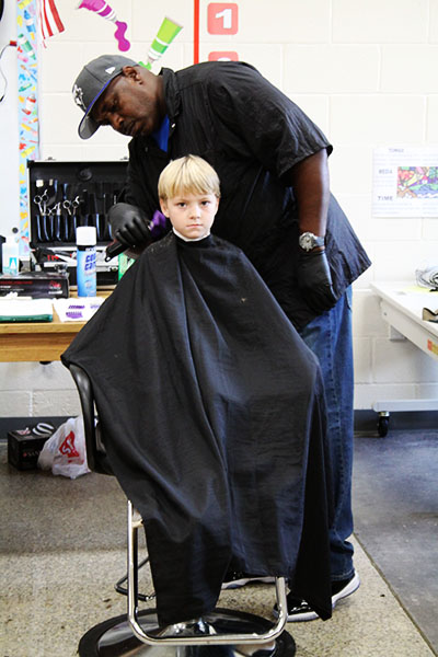 Rodney Taylor, a barbering student at CGTC cuts Nathan Stripling's hair at the Houston County Board of Education's 8th Annual Back2School Bash.