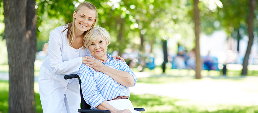 Nurse and senior patient in a wheelchair looking at camera outside