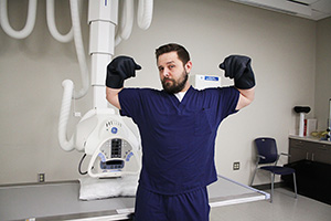 Male radiologic technology student giving a strong man pose