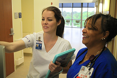 Female student nurse engages with professional nurse.