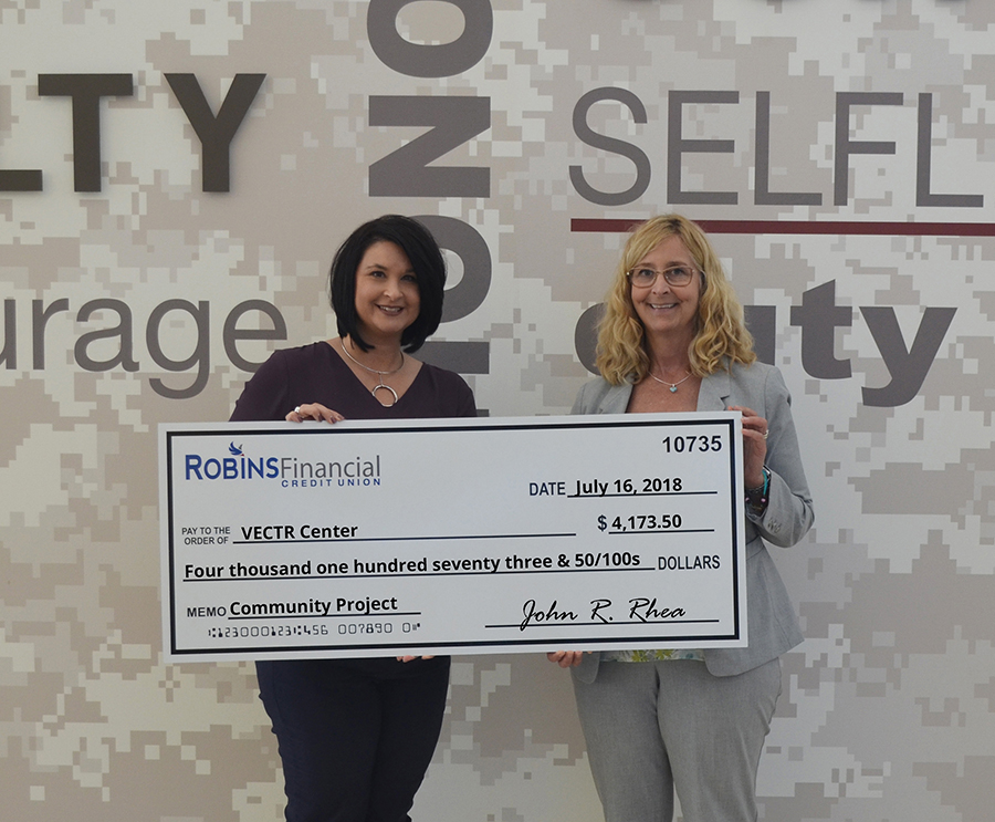 Executive vice president for Robins Financial, Christina O'Brien, presents a check to the Georgia VECTR Center's chief operating officer, Col. Patricia Ross (Ret.).