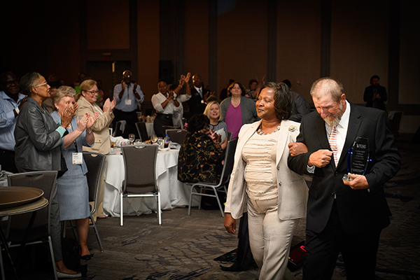 (Courtesy of TCSG)2018 Golden GED® Graduate, Thomas Shepler, walks to a standing ovation with, Dorothy Ferguson, director of Operations for the College's Adult Education Division, following his speech at the TCSG 2018 Adult Education Fall Conference and GED® Awards.