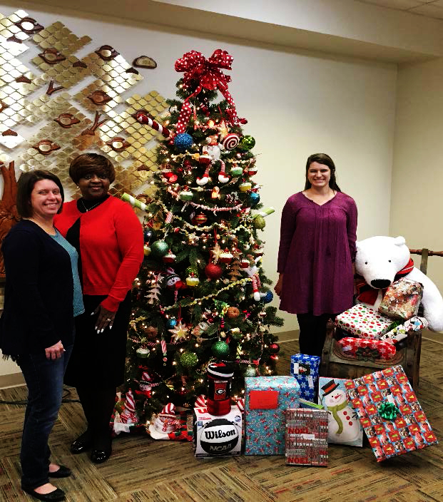 (From Left to Right) Elizabeth Eader, director of Campus Life at The Methodist Home, Ruby Holmes, project manager at CGTC, and Brittany Grier, marketing coordinator at The Methodist Home, set gifts donated by CGTC's Institutional Effectiveness staff next to a Christmas tree at the Methodist Home for Children and Youth.