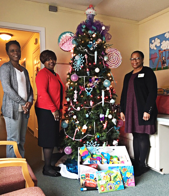 (From Left to Right) Dr. Tiffany Spivey, special projects case manager at CGTC,  Ruby Holmes, project manager at CGTC, and Tanya Zellner, the executive director at Rainbow House CRC, gather next to a Christmas tree and gifts donated by CGTC's Institutional Effectiveness staff.