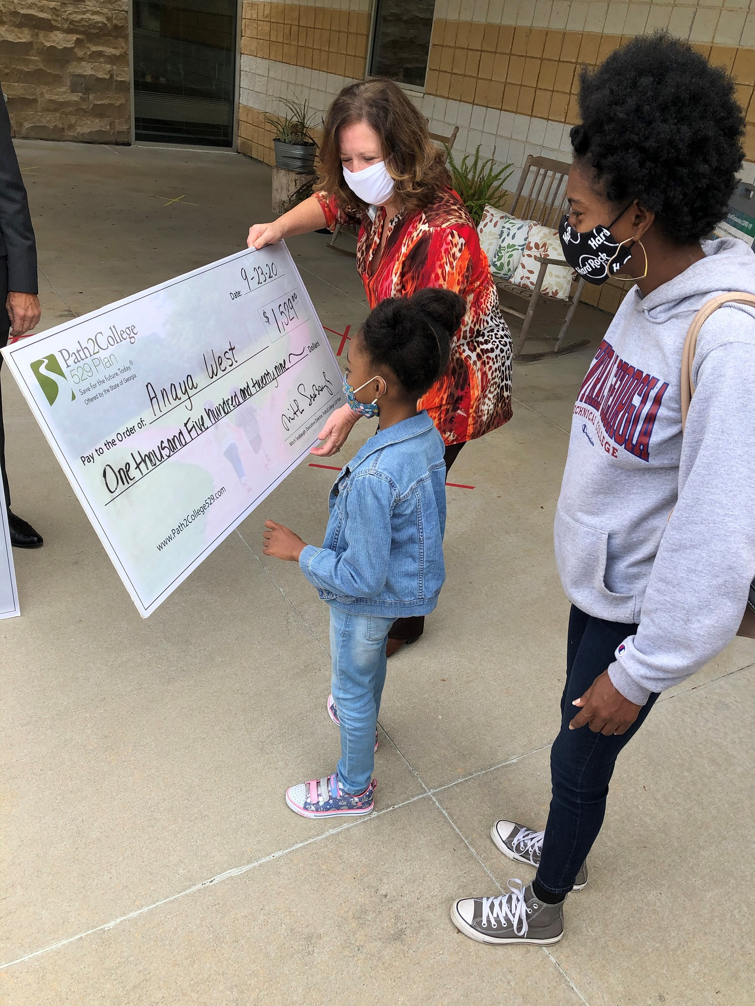 Anaya West looks at her college savings plan check alongside her mother, Adria a student in Construction Management and Center director, Linda Smith.