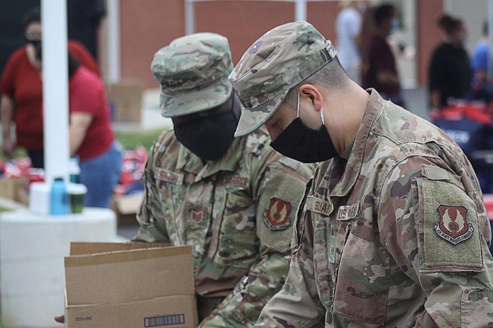 Military personnel help distribute goods at VECTR Center Veterans Appreciation Event.