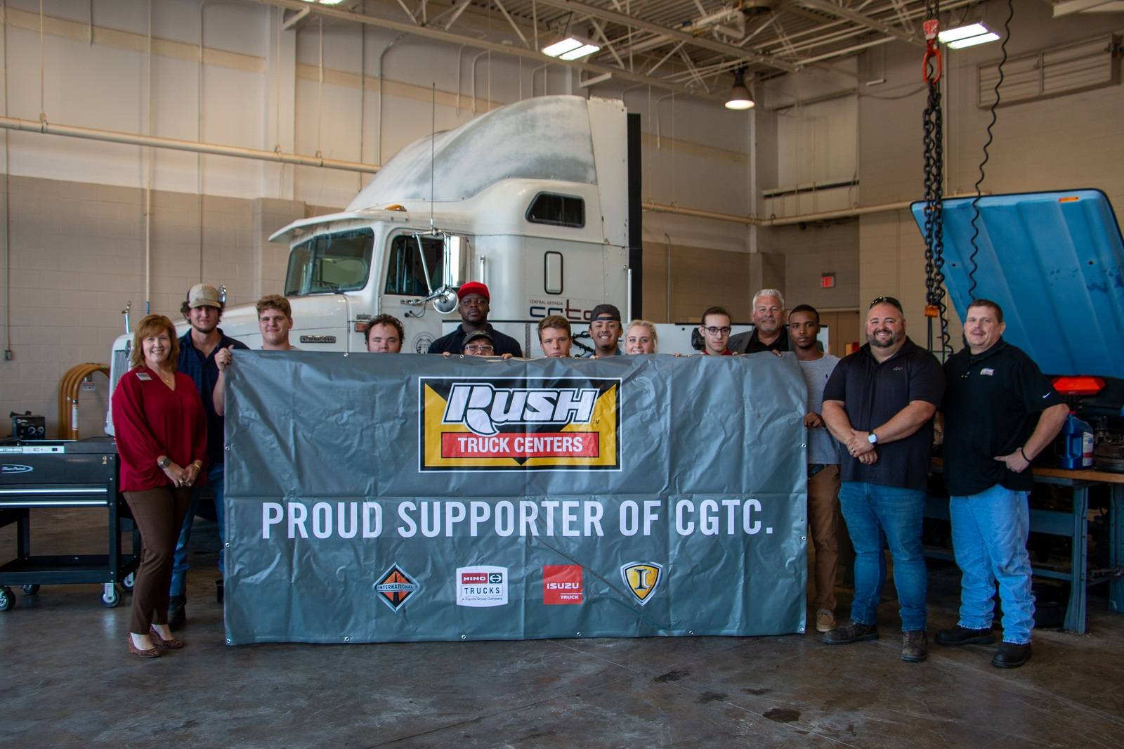 Students, faculty and staff from the Diesel Equipment Technology program and the College hold up a new banner. Rush Truck Centers of Macon recently donated new equipment to the program in September.